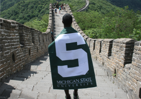 Student with an MSU flag walking on the Great Wall of China